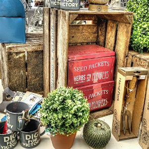 Stall of an antique market with wooden crates, greenery, and red tin boxes