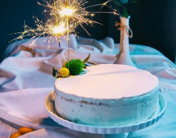 White cake on a pedestal topped with lit sparklers