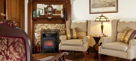 Beautiful room featuring an old fireplace with fire stove in front and two upholstered wing back chairs