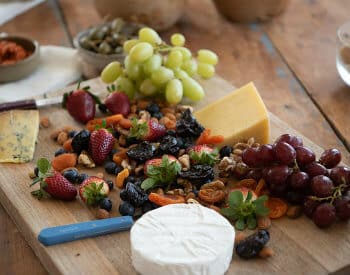 Wood board topped with red and green grapes, cheese wedges, berries and nuts