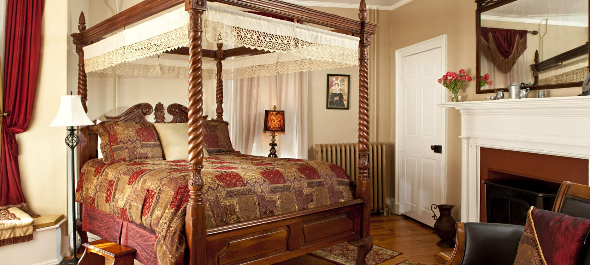 Beautifully elegant guest room with four poster bed; red, brown and gold bedding; and fireplace