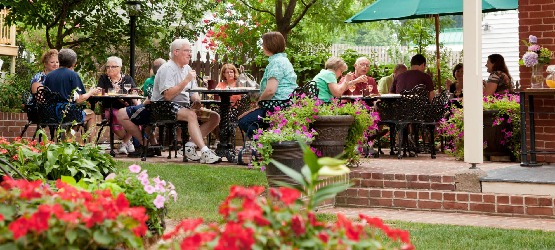 Guests sitting outside at patio tables smiling and eating amidst a grassy lawn and bright flowers