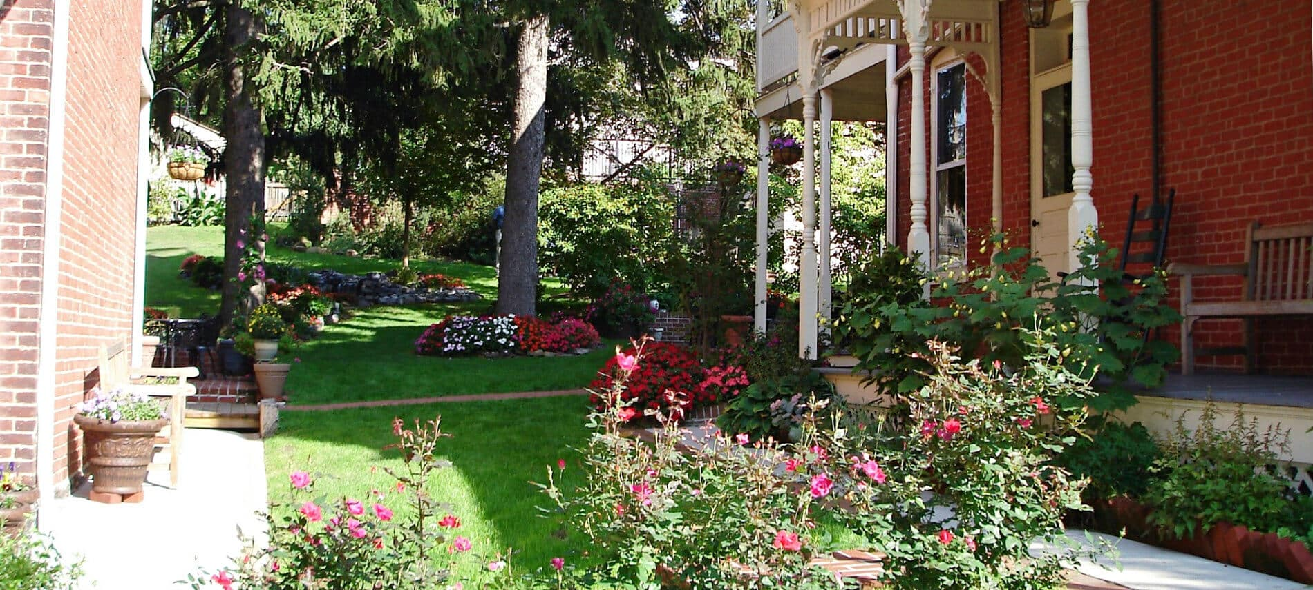Brickhouse Inn side yard covered with green grass, colorful flowers and shade trees