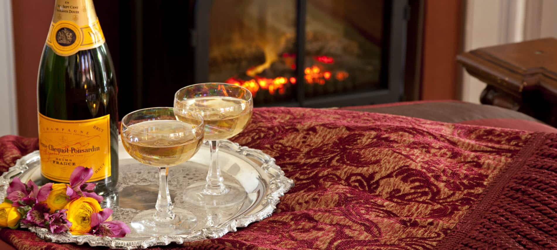 Silver tray topped with wine and two wine glasses near a glowing fire
