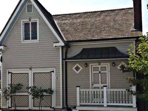 Cricket House cottage rental exterior with grayish beige siding, steep gable, white trim, and front porch with white railing
