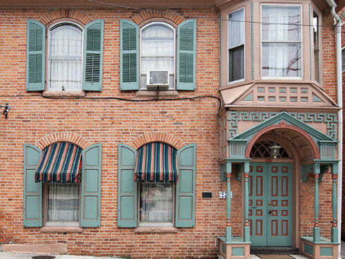 Stahle House rental exterior with brownish orange brick, turquoise shutters and trim, bay window and portico