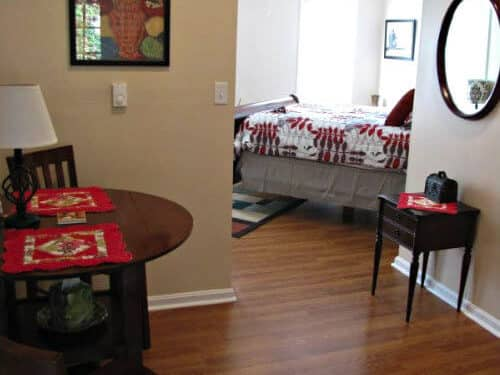 Guest rental with tan walls, hardwood floors, dinette for two and view of guest room
