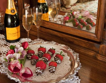 Doily-lined tray topped with chocolate covered strawberries next to champagne bottle and two flutes