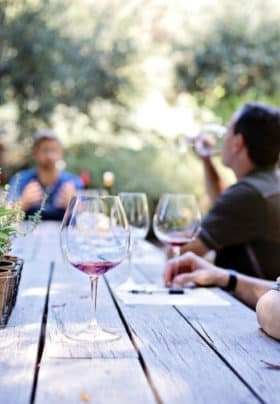 People sitting at picnic tables outside enjoying wine tasting
