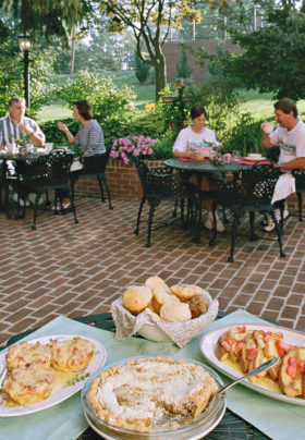 Guests sitting outside at patio tables eating with a table full of delicious baked goods