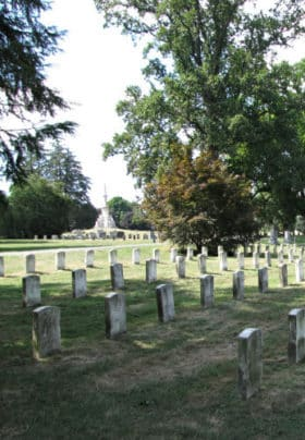 Gettysburg Cemetery with rows of old headstones surrounded by grass and trees