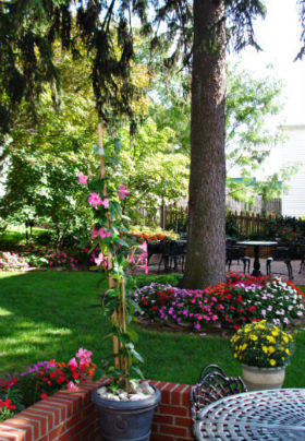 Lush green lawn full of trees and bright colorful flowers and two patios with seating