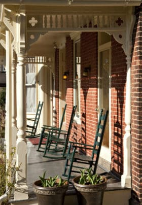 Front porch with brick walls, ivory posts and trim, and green rocking chairs