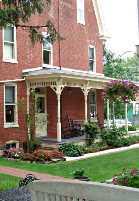 Outside view of the Brickhouse Inn with lush green lawn and bright colorful flowers