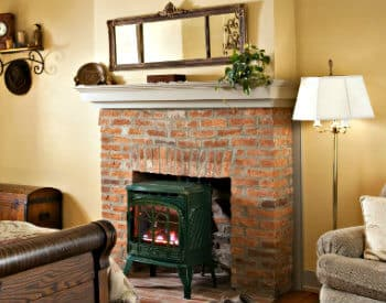 Old brick fireplace with green fire stove in front